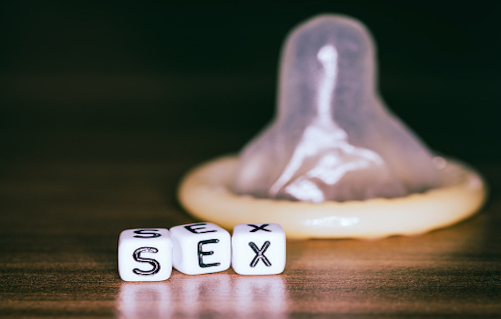 "blocks spelling out ""sex"" in the foreground with a condom in the background"