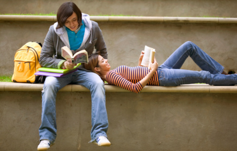 Image of teen couple reading books. A males is sitting and a female is laying down on a level.