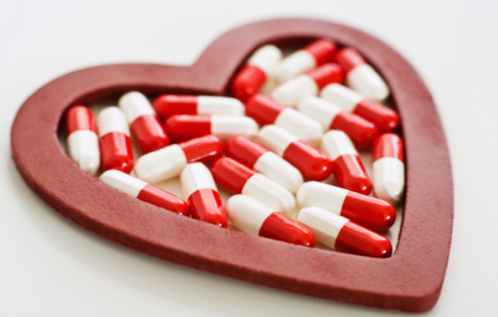 Image of a pink heart containing red an white pills on a white background.