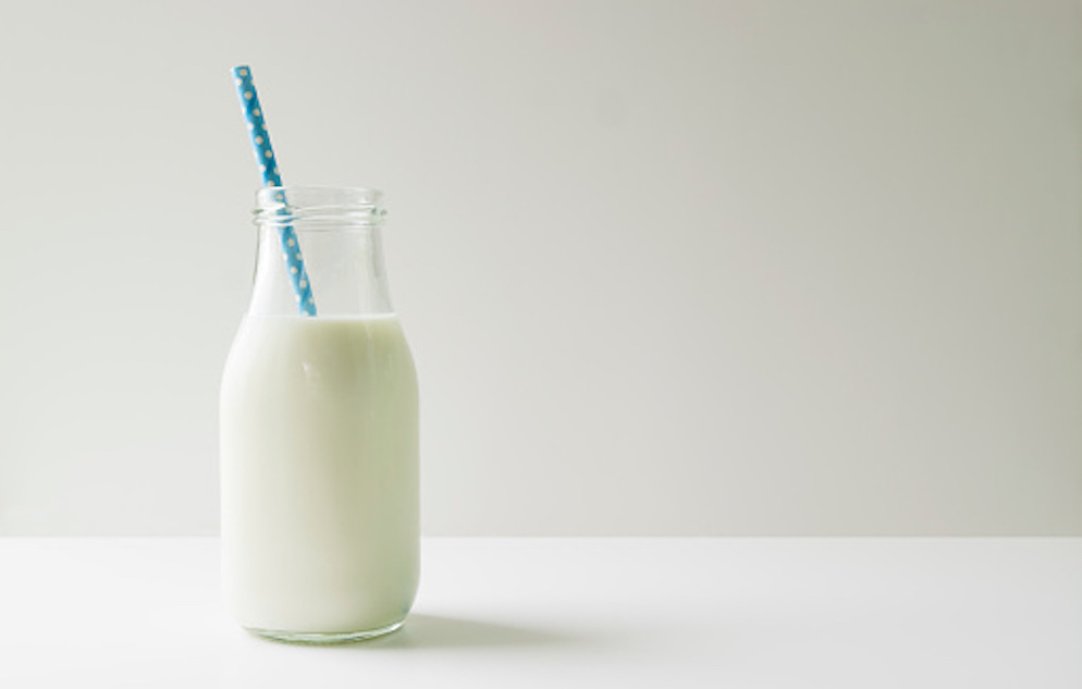 Clear, glass bottle of milk with a blue polka a dot straw set against a white backdrop