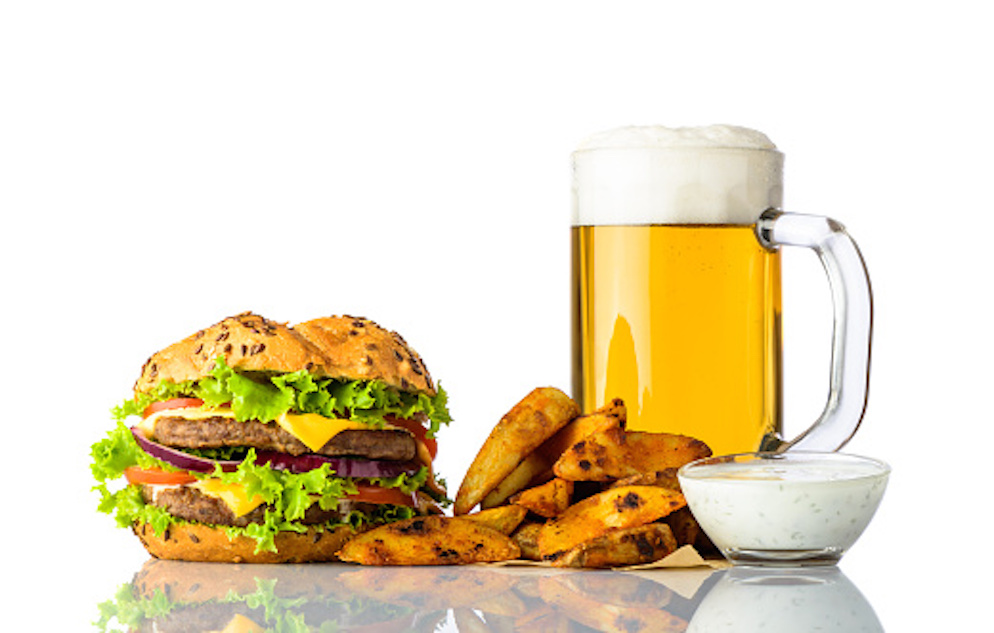 Image of a burger, fries, beer, and sauce.
