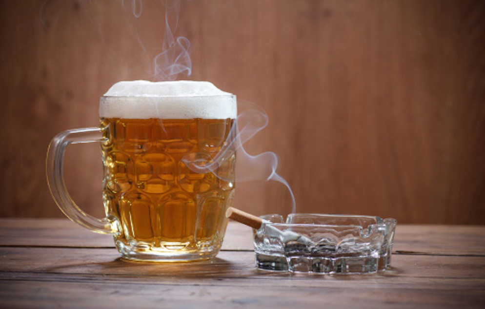 Clear mug of beer next to a smoking cigarette on a clear astray atop wooden surface.