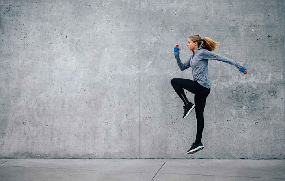 Female jumping in a running pose in front of a concrete wall.