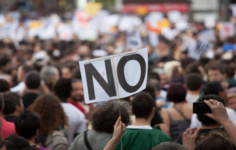 "White rectangular sign with black text in capital letters reading ""NO"" being held on a stick atop a multitude of people extending into the backdrop."