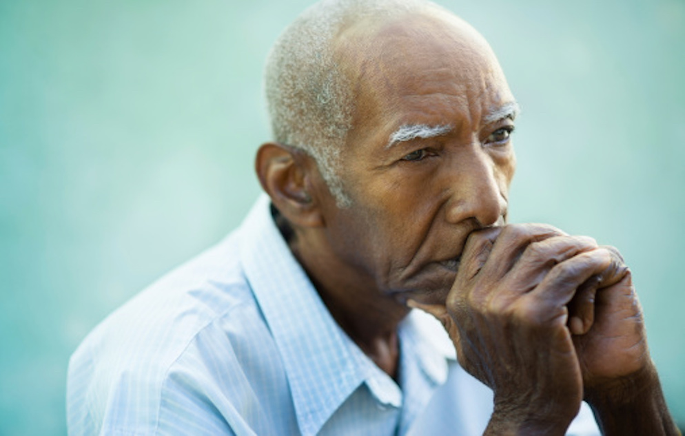 Photo of old African American man with his chin resting on his folded hands and thumb