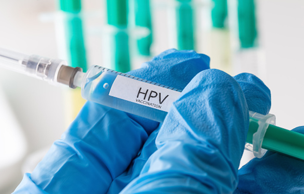 Fingers covered in blue gloves and holding a clear and teal syringe with a white label that reads: HPV VACCINATION