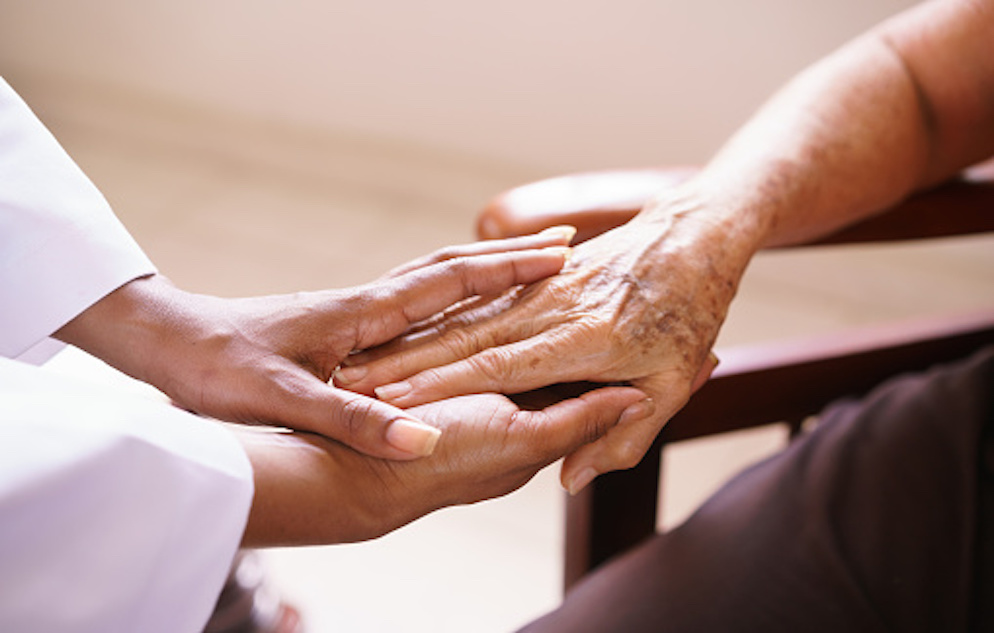 A caregiver's hands holding the hands of an elderly person.