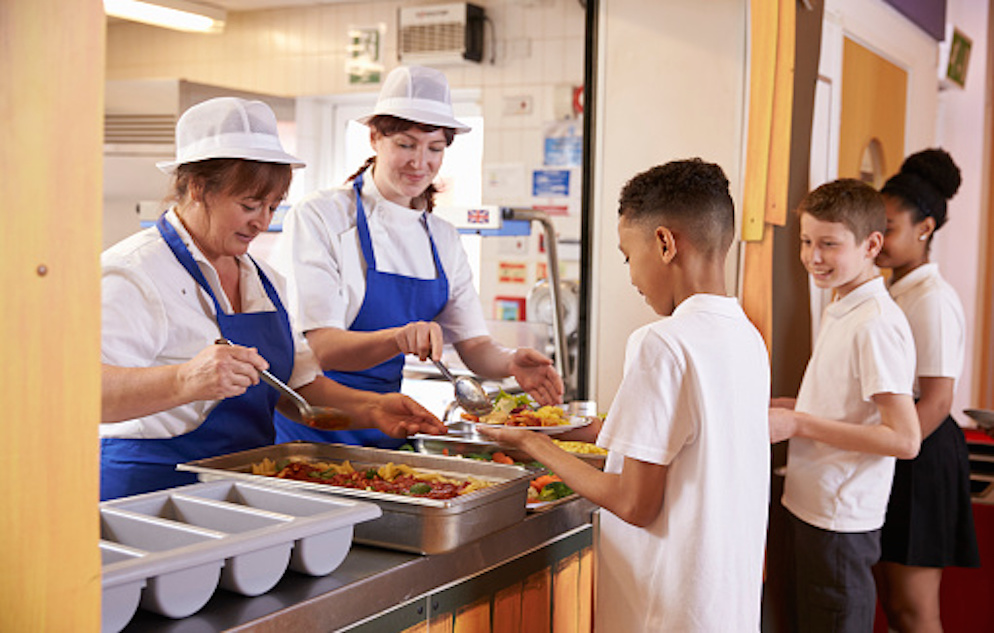 Two women serving food to a boy in a school cafeteria. The women are wearing white chef's uniforms, white hats, and blue aprons. The boy is in a lunch line with one other boy and one girl.