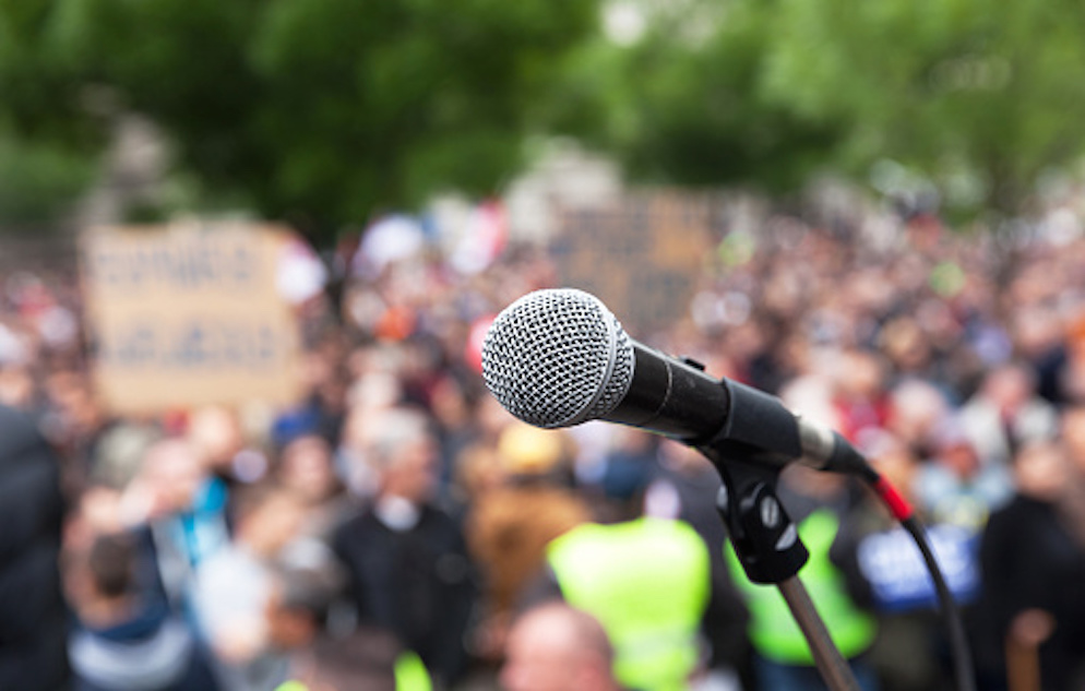 Close up and clear image of a microphone with a crowd of people in the background. The crowd in the background is out of focus.