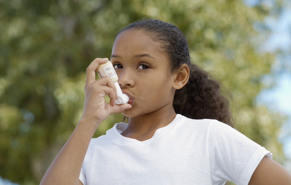 Girl (7-9) using inhaler, outdoors