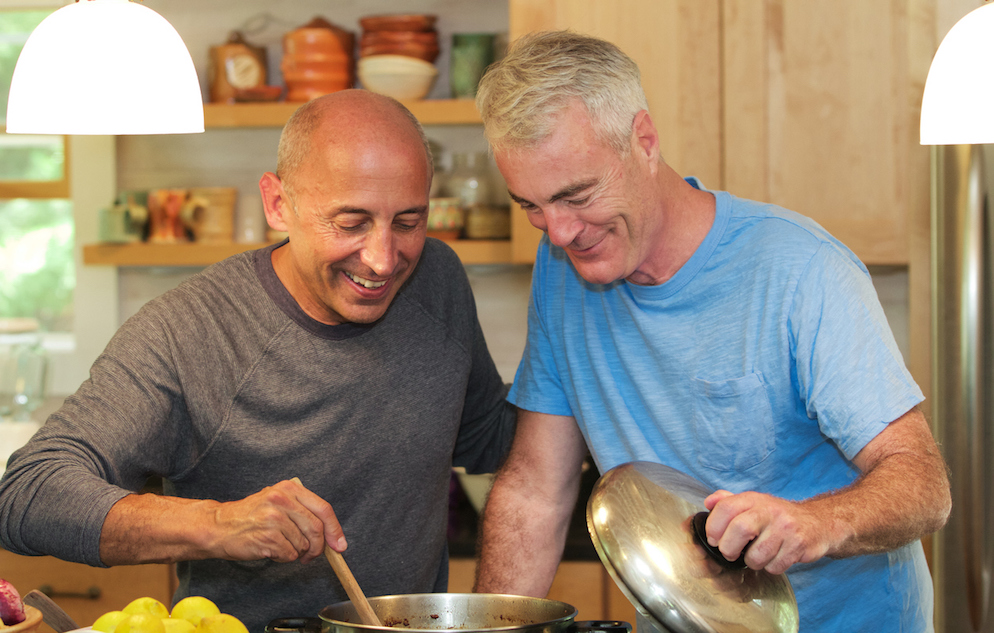 Senior gay male couple at home cooking together and smiling