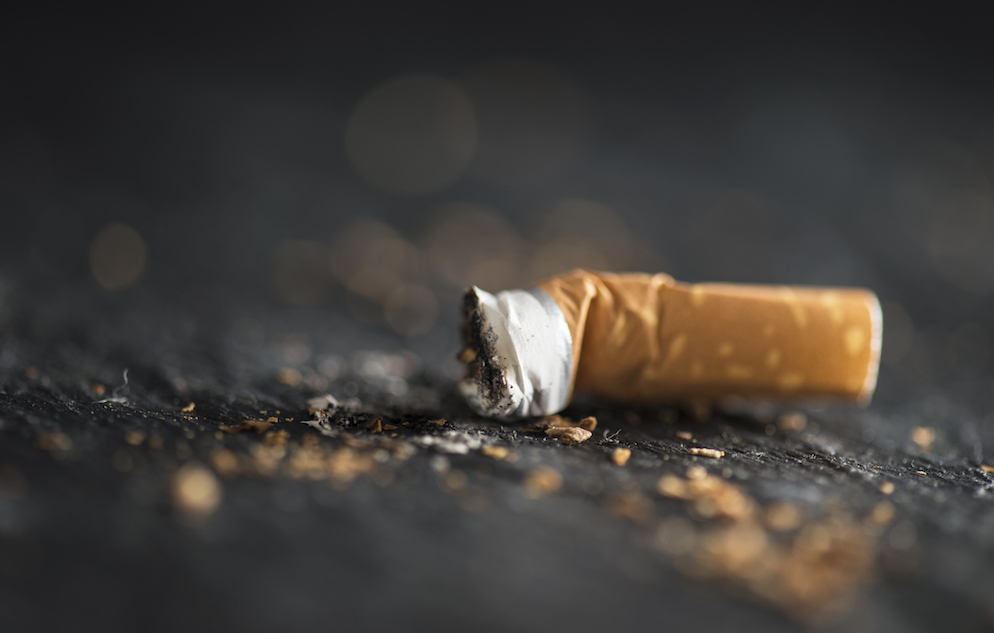Cigarette butt on dark abstract background.