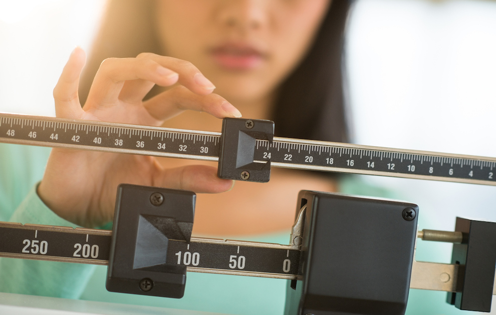 Adult woman with dark hair adjusting the balance of a weight scale