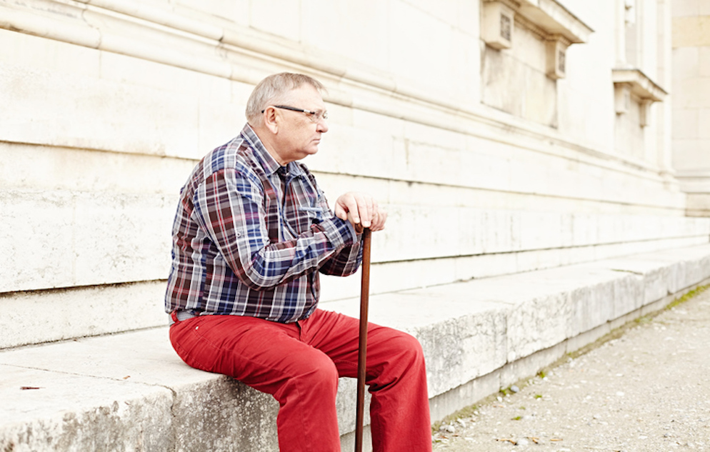 Portrait of mature man in glasses and plaid shirt resting leaning on his wooden walking stick