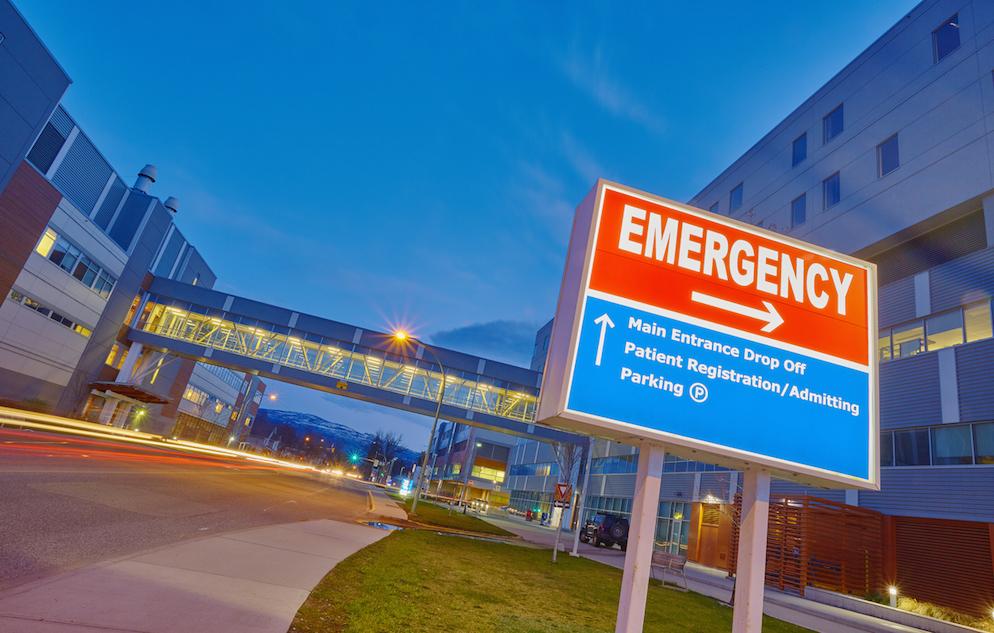 Emergency sign against hospital background.