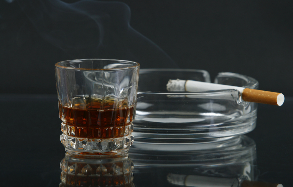 Glass of whiskey and cigarette in an ashtray