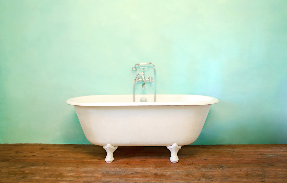 Vintage bathtub in front of a green wall