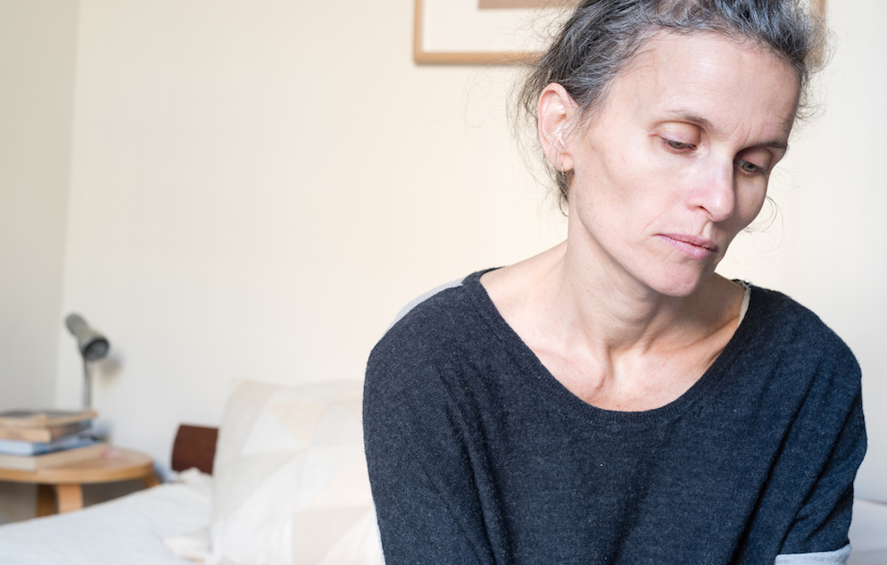 Middle aged woman in bedroom looking sad and depressed