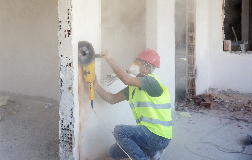 Construction worker working on the wall with saw