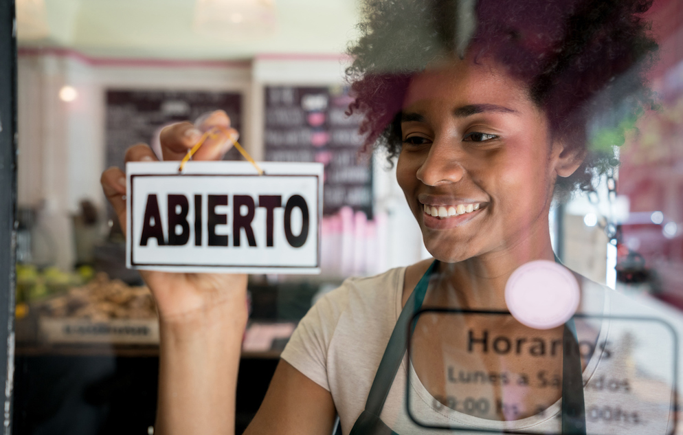 Portrait of a beautiful african american business owner of a cafe hanging an open sign on the door smiling