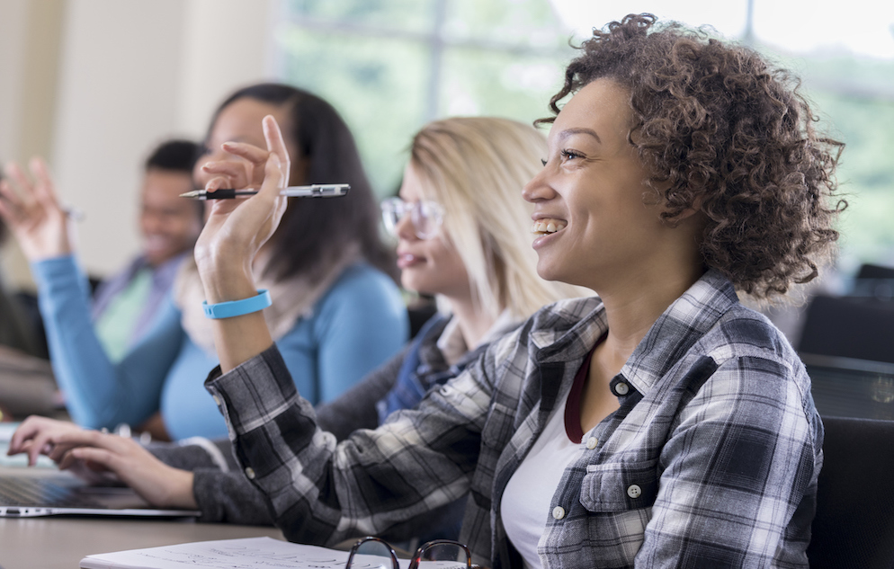female students raise hands in class