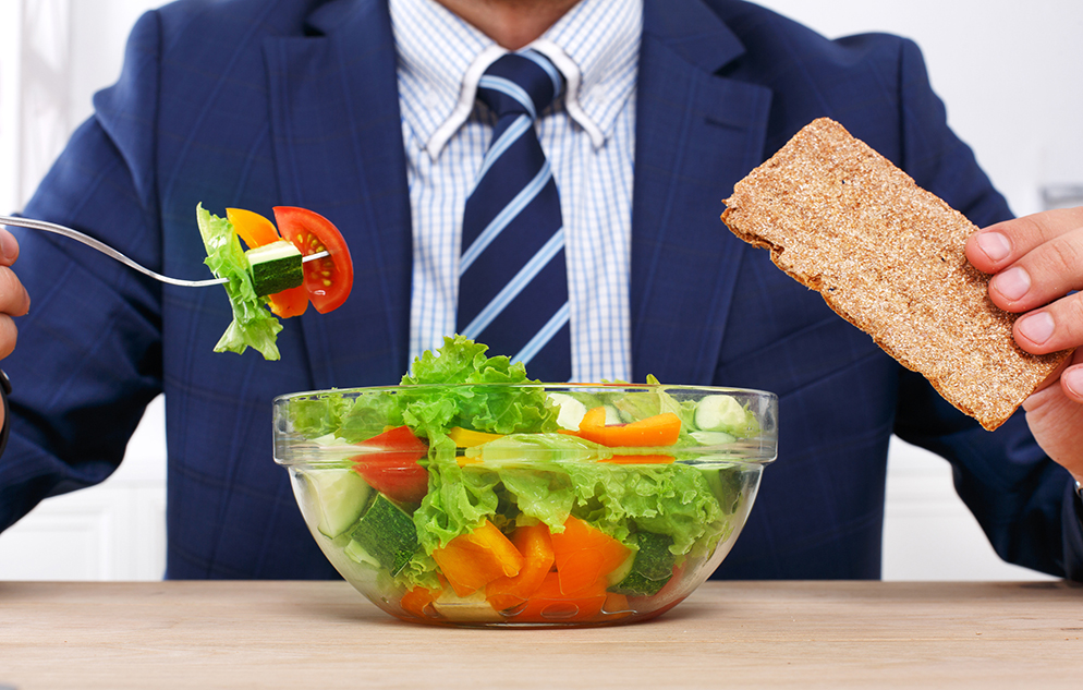 man in a suit eats a salad at a desk