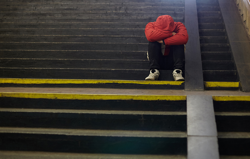 young man sitting on subway stairs with head in hands