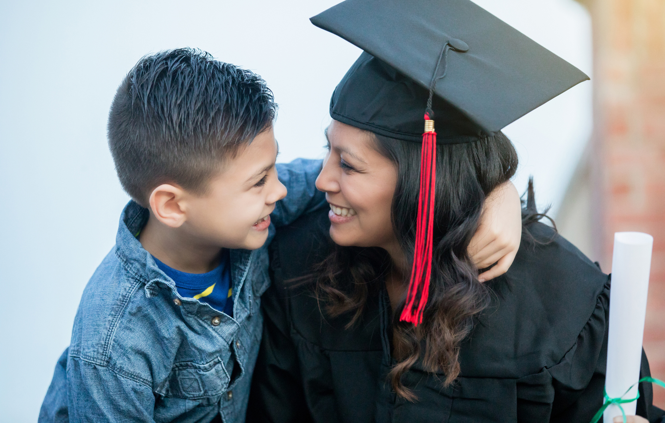Woman wearing graduation cap and gown sitting with a child