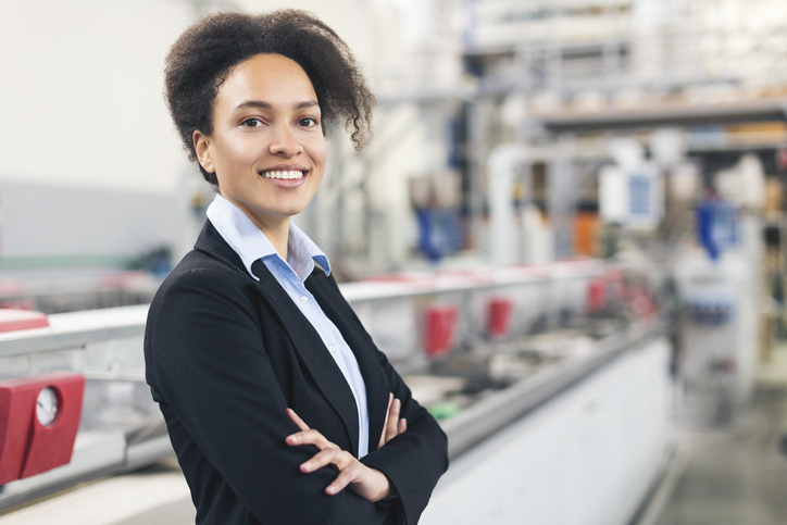 Woman smiling while standing in factory