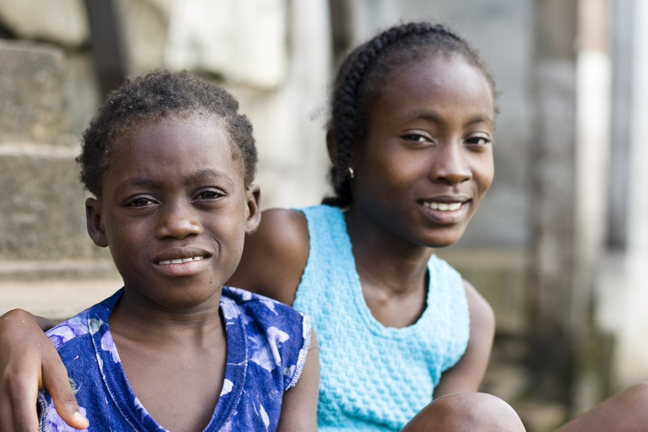 Two African girls smiling at the camera.