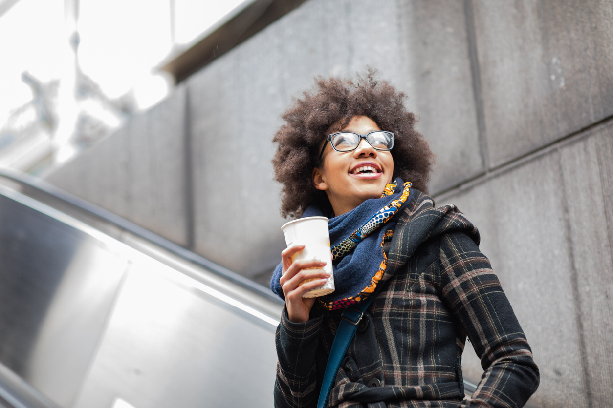 Smiling young woman holding coffee on escalator