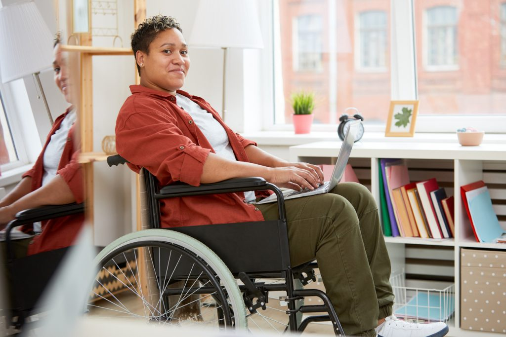Woman in wheelchair typing on laptop