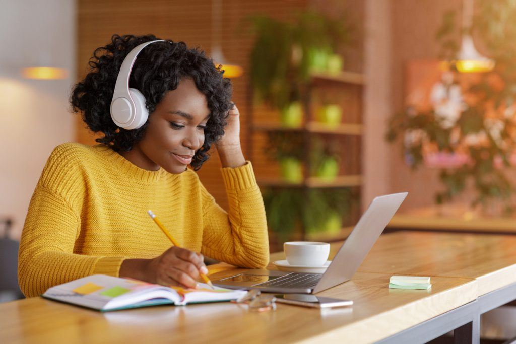 Student wearing headphones and engaging in online learning