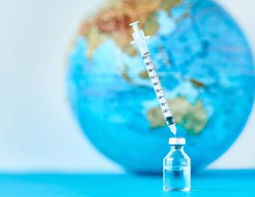 vaccine vial in front of globe