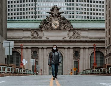 Woman wearing face mask walking in front of Grand Central Station in NYC