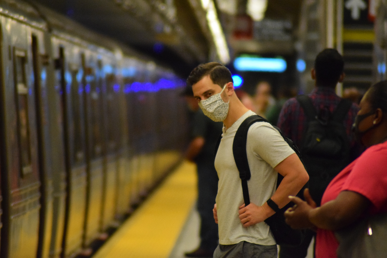 masked man waits for train