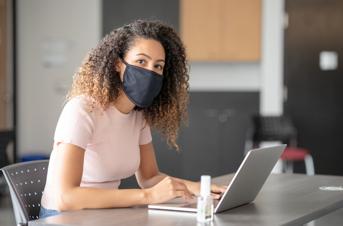 student wearing face mask works on laptop