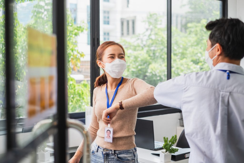 two employees at work wearing face masks and bumping elbows
