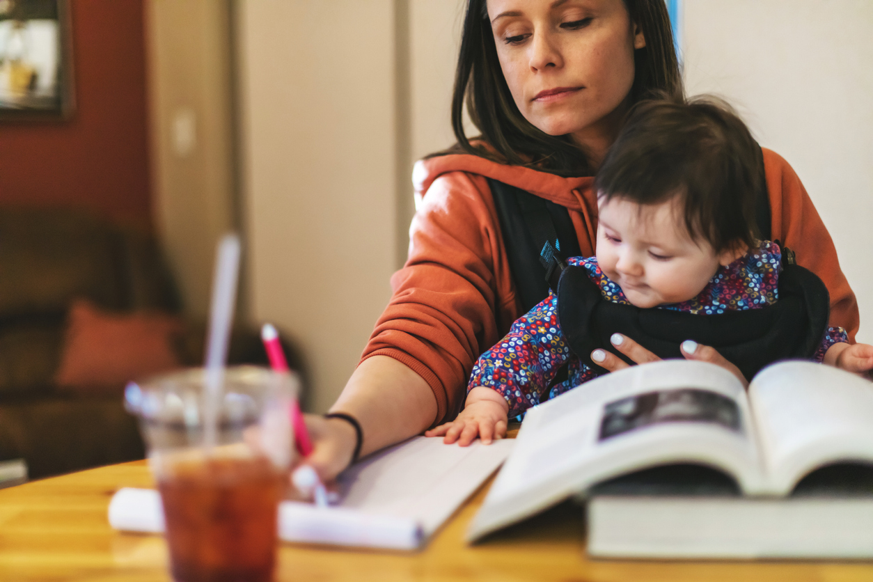 woman studying with baby in carrier